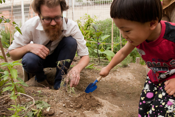 Patrick works with Kenji in the garden