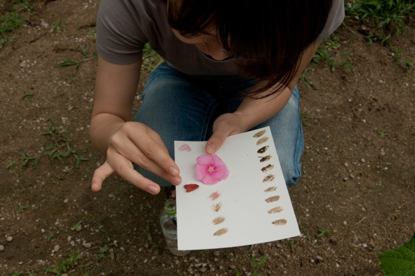 Participant in the Final Straw's Soil Art workshop uses soil and flowers to create a color chart in Osaka, Japan